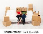 Couple in their new home with cardboard boxes, sitting on covered sofa - stock photo