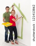 Couple dreaming up their new home - painting it on the wall - stock photo