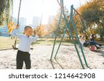 children ride on a swing in... | Shutterstock . vector #1214642908