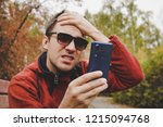 young guy reads news or sms on... | Shutterstock . vector #1215094768