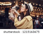 Stock photo kissing puppy happy young pretty lady standing outdoors with hat on her head and kissing cute 1215163675