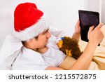 young man in santa hat with a... | Shutterstock . vector #1215572875