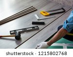 man installs new laminate... | Shutterstock . vector #1215802768