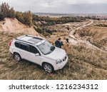 couple standing near suv car at ... | Shutterstock . vector #1216234312