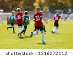 boys kicking football on the... | Shutterstock . vector #1216272112