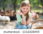 young girl holding chicken eggs ... | Shutterstock . vector #1216328455