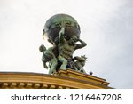 Small photo of The titan called Atlas is carrying the world on his shoulders. Greek mythotology figure as part of the historical train station roof built in 1888 in Frankfurt, Germany.
