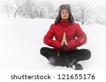 Woman meditating in the lotus position in winter - stock photo