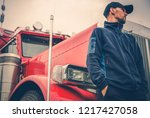 Caucasian Trucker in his 30s in Front of His Red Shiny Semi Truck. Light Rainy Weather. Occupation Truck Driver. - stock photo
