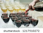 red wine pouring into a wine... | Shutterstock . vector #1217510272