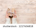 woman hands give wrapped... | Shutterstock . vector #1217636818