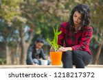 young woman planting a small... | Shutterstock . vector #1218217372