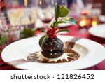 Christmas pudding on a decorated plate and berries - stock photo
