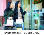 two female friends looking into the shop window - stock photo