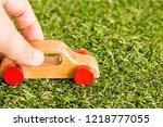 hand hold wooden car on grass... | Shutterstock . vector #1218777055