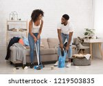 Stock photo young african american man and woman cleaning messy room after party smiling to each other 1219503835