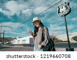beautiful happy teenage girl standing over route 66 background on sunny day and blue sky. young woman using cellphone texting message app standing on quiet road. backpacker traveling outdoors in us.
