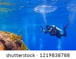 Small photo of Scuba diver with underwater camera on the coral reef. Shallow sea with diver, reef and bubbles. Diver in the ocean and bubble ring on the water surface. Scuba diving in the sea with marine wildlife.