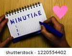 Small photo of Text sign showing Minutiae. Conceptual photo small precise or trivial details of something product or service Man holding marker notebook page heart romantic messages wooden table.