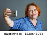mature woman uses a smartphone... | Shutterstock . vector #1220648068