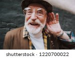 Small photo of Concept of positive mood lifestyle of hearing impaired person. Close up portrait of happy pensioner with playful glance holding palm near his ear