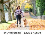 Stock photo woman walking golden retriever dog in fall leaves 1221171505