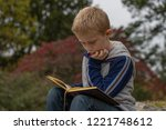 Boy Is Reading A Book In A Park....