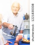 Small photo of Gallant senior man pouring coffee to his female guest at home