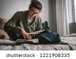 student sitting on a bed and... | Shutterstock . vector #1221908335