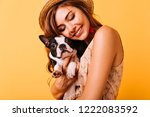 Stock photo relaxed red haired girl embracing puppy on yellow background studio portrait of white appealing 1222083592