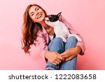 Stock photo laughing jocund woman sitting on the floor with dog on her knees indoor photo of pleasant lady 1222083658