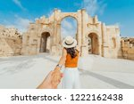 Small photo of Asian young woman tourist in color dress and hat leading man to South gate of the Ancient Roman city of Gerasa, modern Jerash, Jordan. Traveling together. Follow me.