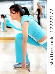 beautiful woman at the gym doing stretching exercise - stock photo