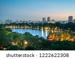 Hoan Kiem lake or Sword lake, Ho Guom in Hanoi, Vietnam with Turtle Tower, green trees and buildings on horizon, at twilight period