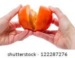 Hands breaking open a persimmon isolated on white background - stock photo