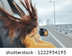 Small photo of Rear view of pre teen girl in car looking forward on a bridge at weekend road trip