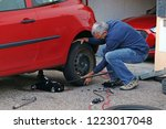 a man changes tires on a car....   Shutterstock . vector #1223017048