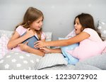 kids lay in bed fight for book. ... | Shutterstock . vector #1223072902