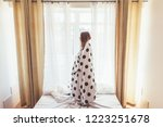 girl wrapped into duvet looking ... | Shutterstock . vector #1223251678