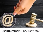 Small photo of Judge's hammer and email address. The concept of legal proceedings for the seizure of rights to use the names of mail and websites. Confiscation of domain names and e-mail. Rights holders.