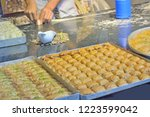 man twists dough in baklava in... | Shutterstock . vector #1223599042