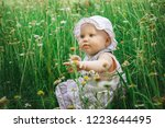 baby girl sitting in the green...   Shutterstock . vector #1223644495