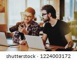 smiling guys use laptops while... | Shutterstock . vector #1224003172