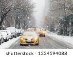 Taxis Drive Down A Snow Covere...