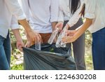 Small photo of Group of People Hands putting recycling waste bit to Black garbage bag collection in park .Environmental CSR Corporate social responsibility concept .