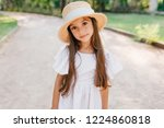 Stock photo little fashionable lady with long eyelashes looking with interest while standing on the road in 1224860818