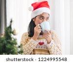 asian woman wearing santa hat... | Shutterstock . vector #1224995548