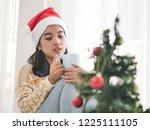 asian woman wearing santa hat... | Shutterstock . vector #1225111105