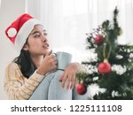 asian woman wearing santa hat... | Shutterstock . vector #1225111108