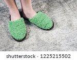 feet in green soft slippers on... | Shutterstock . vector #1225215502